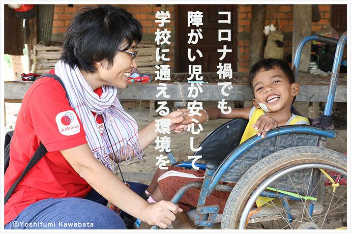 カンボジアの支援現場で、車いすに乗った障がい児が笑顔でAAR職員と手をつないでいる AAR職員は腰をおろし、障がい児と同じ目線に立っている