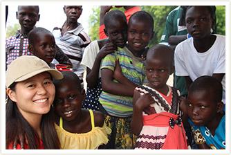 AAR職員と、ウガンダの子どもたち10人近くが笑顔でこちらを向いている