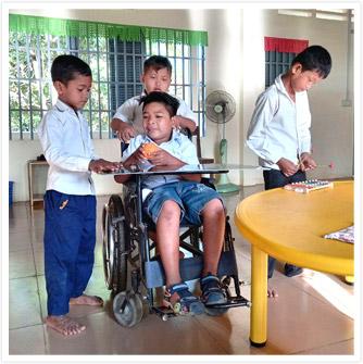 学校の教室で、車いすに乗ったソパナヴィットさんがおもちゃを手にしている 周りには友だちの男の子3名がいて、ソパナヴィットさんの持つおもちゃを見たり、別のおもちゃで遊んでいる