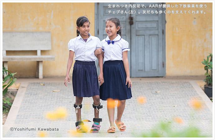 校舎内を、女の子2人が笑顔で歩いている 一人の子は足が不自由で、両足に補助具をつけており、もう一人の子が、その子の歩行を支えるように腕を組み、歩いている