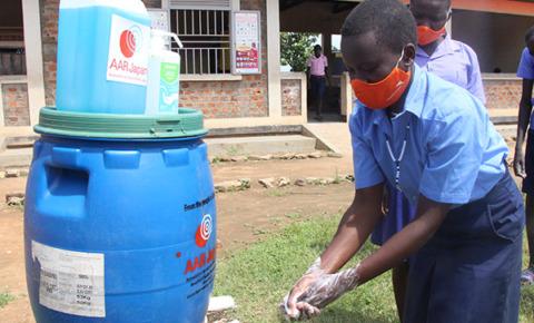ウガンダの学校に通う男の子が水タンクから出る水で手を洗っている