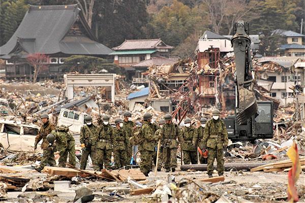 波や地震の被害で瓦礫だらけの市街地を15名ほどの迷彩服を着てマスクをつけた自衛隊員が歩いている