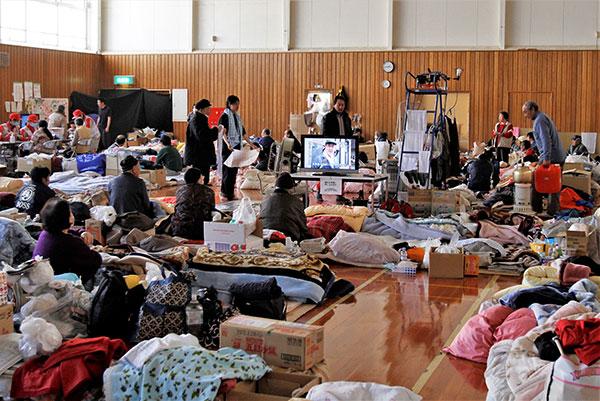 個々の布団、衣類、段ボールなどの荷物が雑然と広がっている避難所 中央にはテレビが設置されている