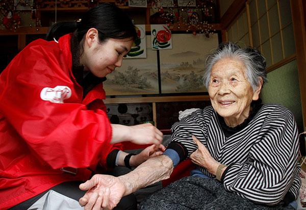 おばあちゃんの自宅で、おばあちゃんの腕に手当てをほどこすAARの女性スタッフ