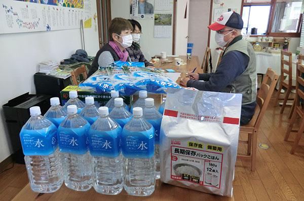 提供した飲料水や保存のきく食糧の近くで話を聞く大原