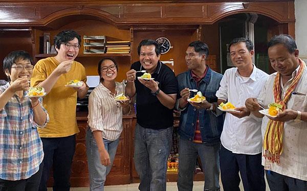 駐在員の山本と向井、現地スタッフの男女5人が笑顔でお祝いのスイーツを食べている