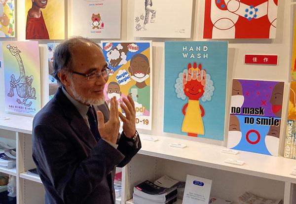 手振りをそえて作品を評価する小林氏 後方にいくつもの作品が展示されている