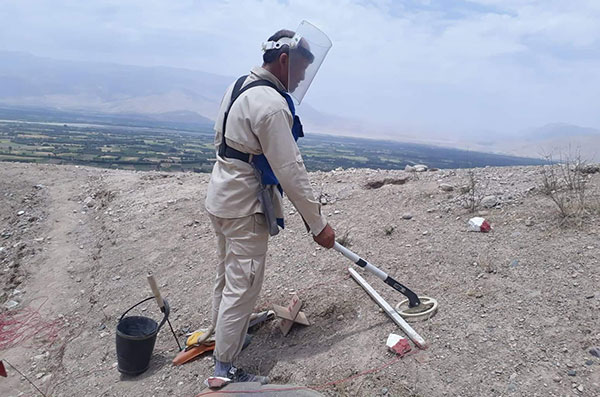頑丈なバイザーを顔に装着し、地雷の探知機を握り、作業に取り組む男性 周辺には建物など何もない切り拓かれた場所