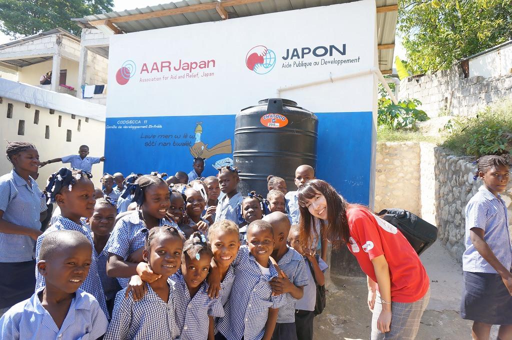 大きな水タンクの前で小学生くらいの子どもたちとともにカメラに向かい微笑む粟村。子どもたちは制服を着ている