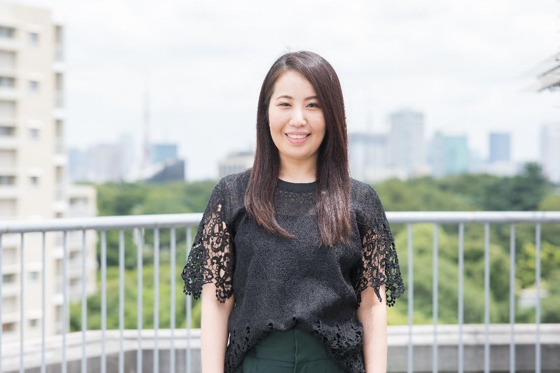 屋上で鎌田がカメラに向かい微笑む