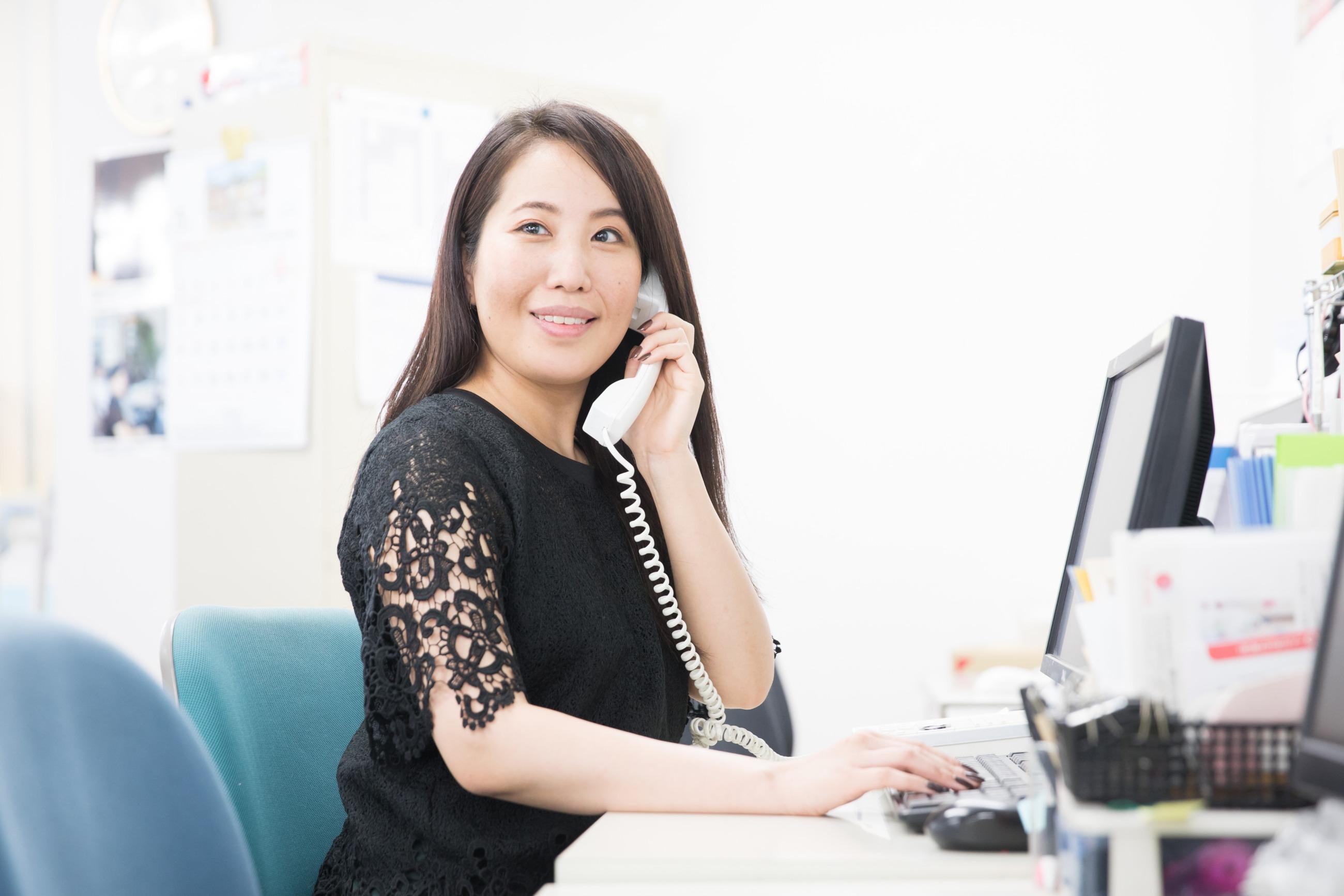 鎌田が電話の受話器を耳にあてて話している