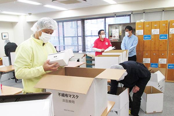 男性数名がマスクの箱を段ボールに梱包している 作業時にゴミなどが入らないよう、頭にキャップをつけるなど衛生対策もしっかりしている