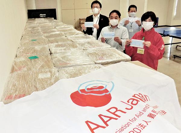 マスクが梱包された段ボールが、目に見えるだけで30箱近く積み上げられている 近くに4人が立っている