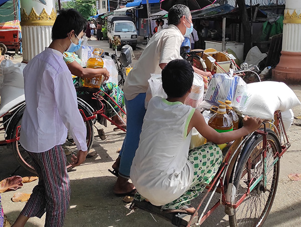 AARから受け取った食料や衛生用品を運ぶ障がい者の家族