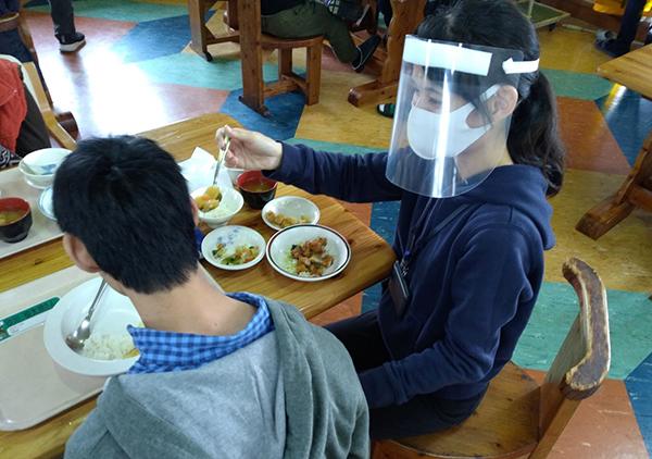 介護者の女性がフェイスシールドをつけて穏やかな表情で利用者の方に食事介助をしている