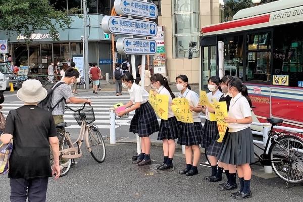 学校の制服姿で、6人の生徒が募金のお願いを記した紙や募金箱を手にし、寄付の呼びかけをしています