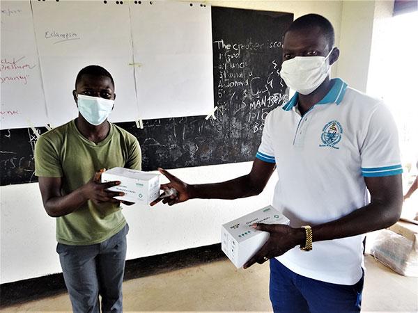 スタッフからコンゴ難民の男性がマスクが入った箱を受け取っている