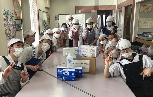 14名の方が机を囲むように集まっている 机上には衛生用品が置かれている