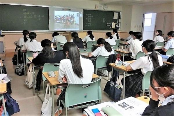 教室前方にあるプロジェクターに写る資料を見つめながら真剣に講義を聞いている生徒たち