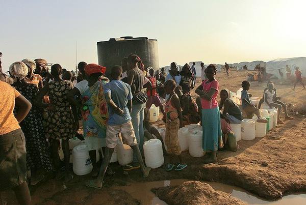 大人や子どもが水タンクなどを手に列をなしている