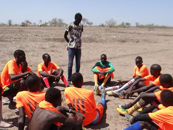 ユニホームを着た難民と地域住民の人々 サッカーの休憩中に戦略を練っている