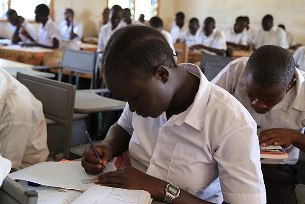 難民の女性アンさんが教室で机に向かって真剣に勉強している