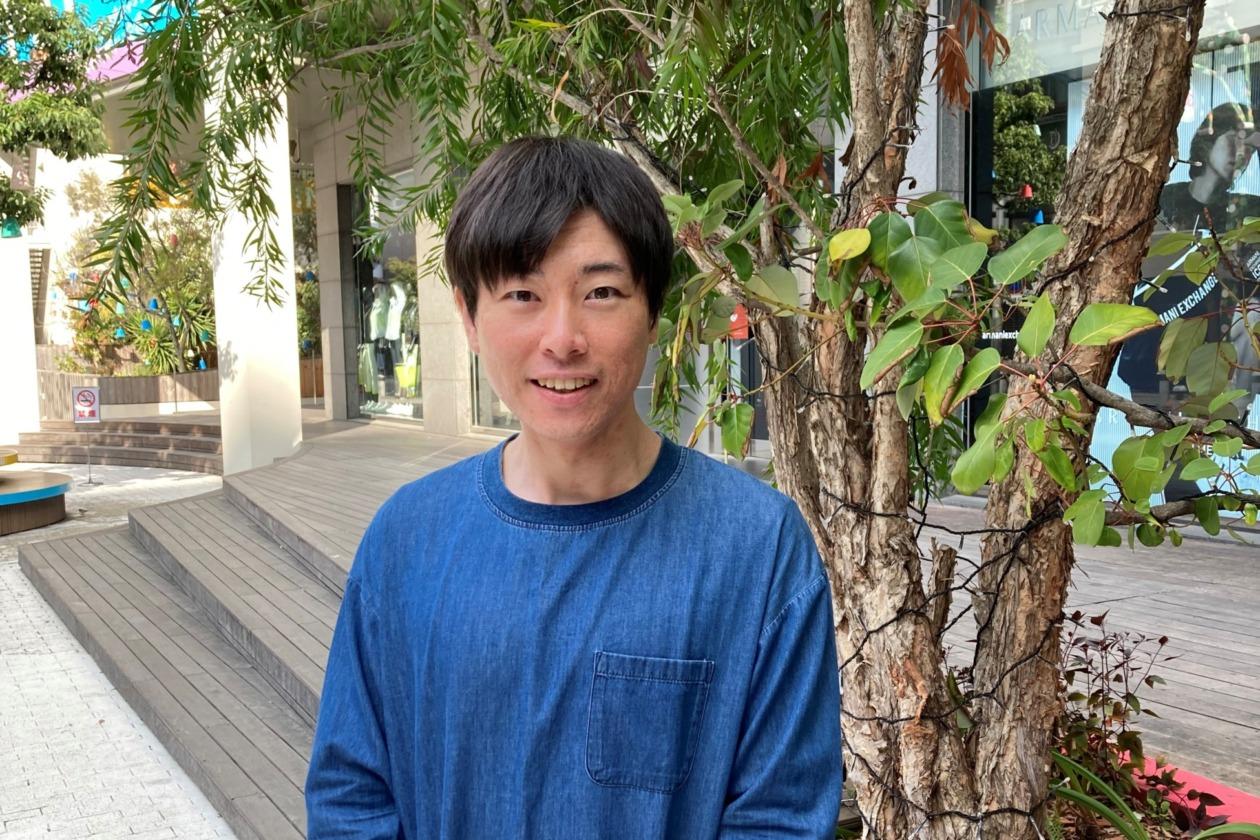 駐在員の宮崎が木の横に立ちカメラに向かい笑顔で微笑む
