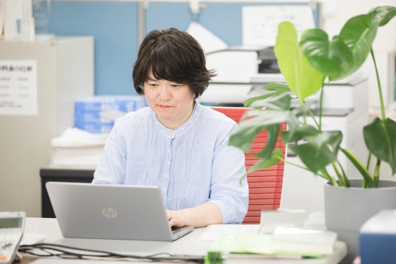 ノートパソコンを開いて作業をする大塚