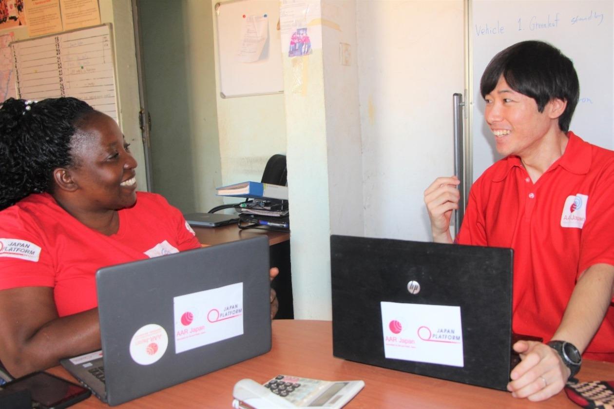 現地スタッフと宮崎が笑顔で会話している。2人の前にはノートパソコンが開いて置いてある