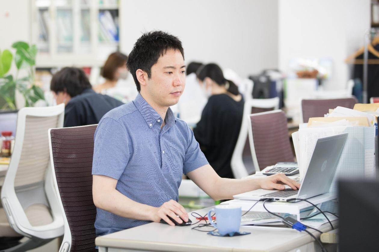 生田目が事務所でパソコンを使い業務をしている