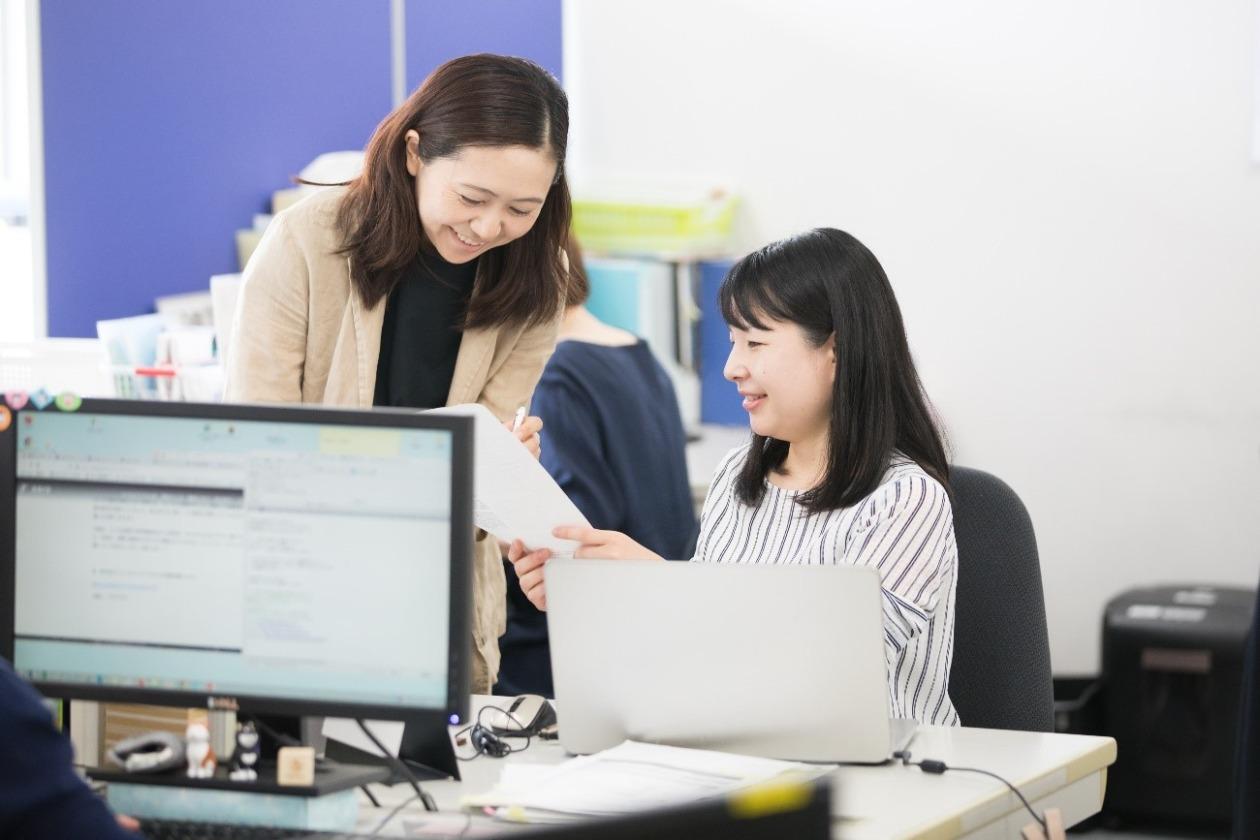 事務所で杉崎が同僚の女性に書類を見せている