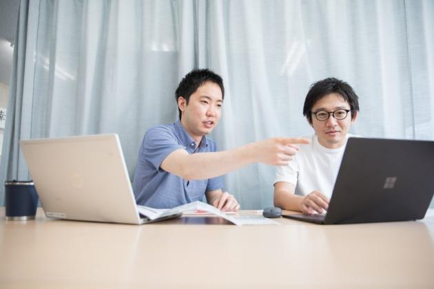 生田目の横に同僚のスタッフが座っている。2人でノートパソコンの画面を見て話し合っている