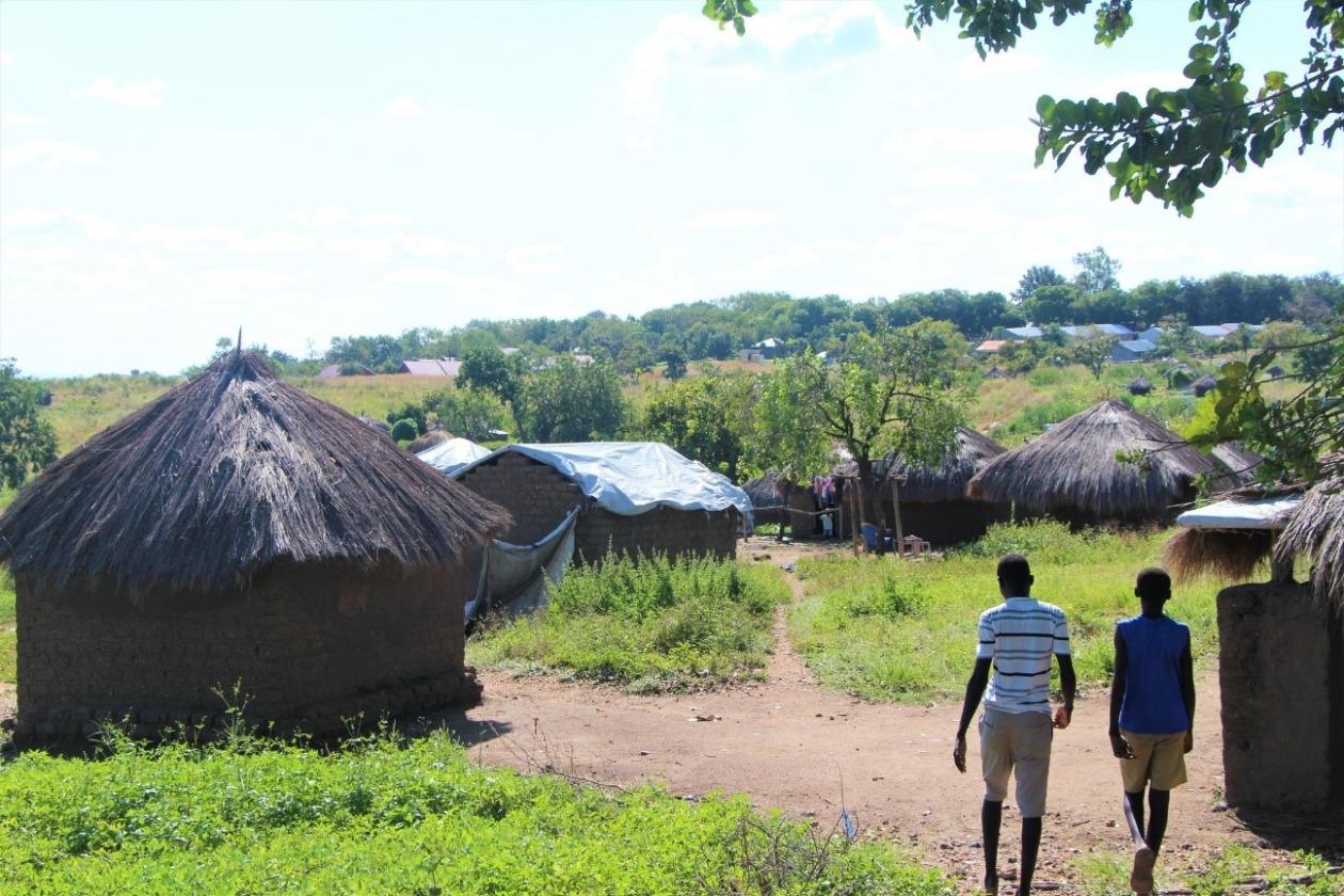かやぶきの屋根の家が4つほど建っている。その横をアフリカに暮らす2人の男性が歩いている