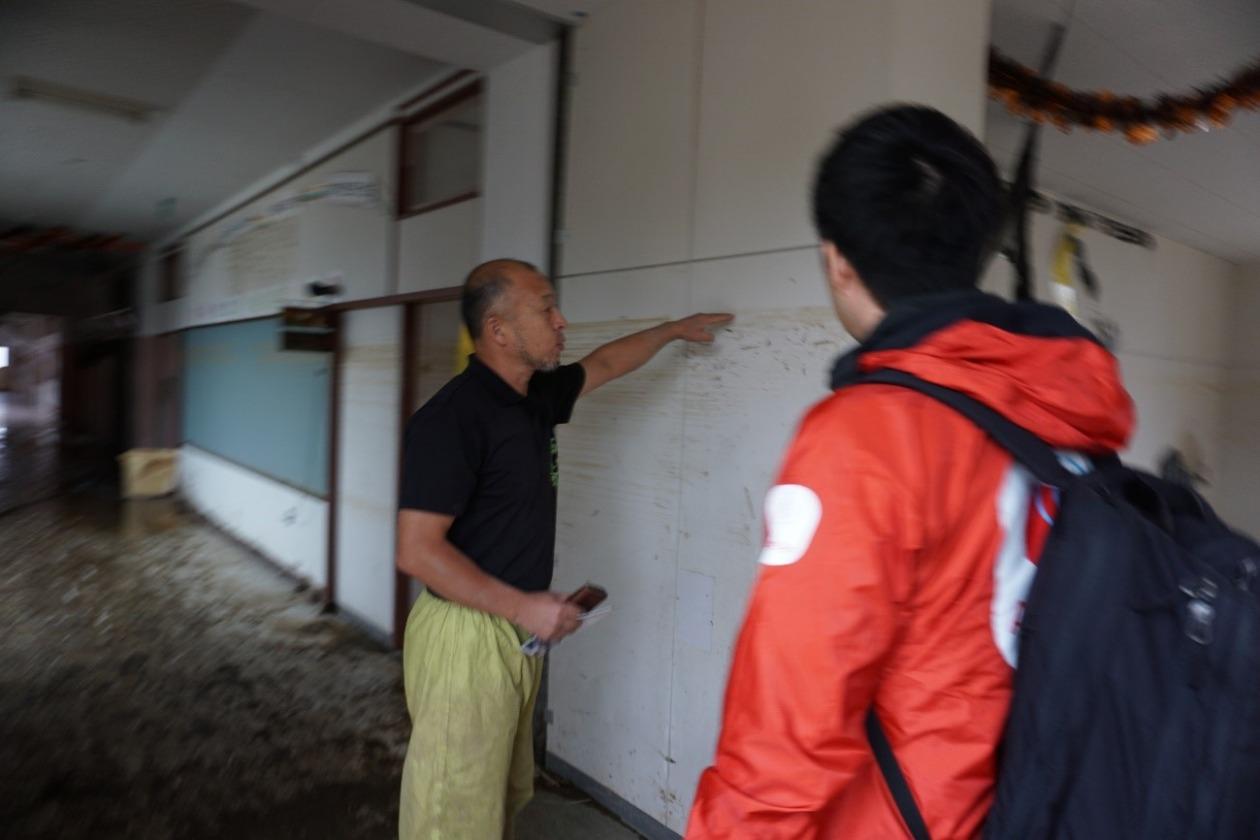 薄暗い福祉施設の中、床には泥がある。男性が壁を指して水があがってきた場所を生田目に伝えている