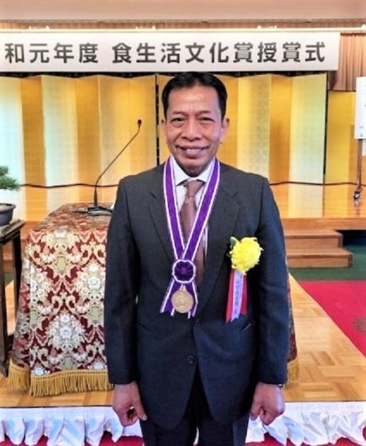 仙田佐武朗さんが食生活文化省の受賞席に出席し、首からメダルを下げて嬉しそうに微笑んでいる