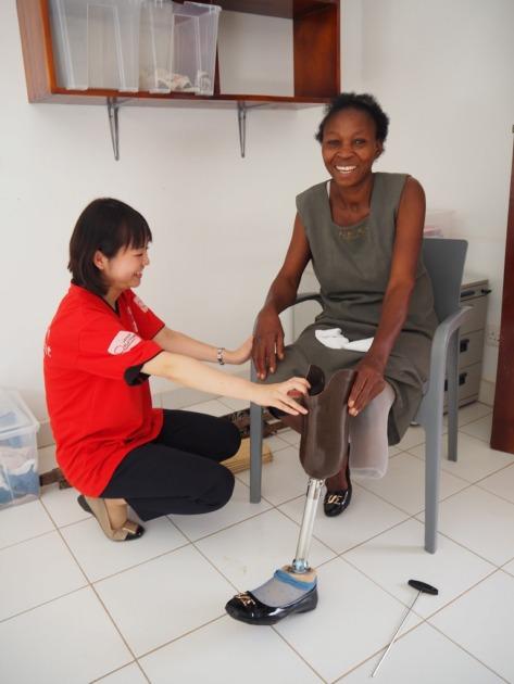 イスに座り義足を装着している女性とその横で膝を着いているAARスタッフ