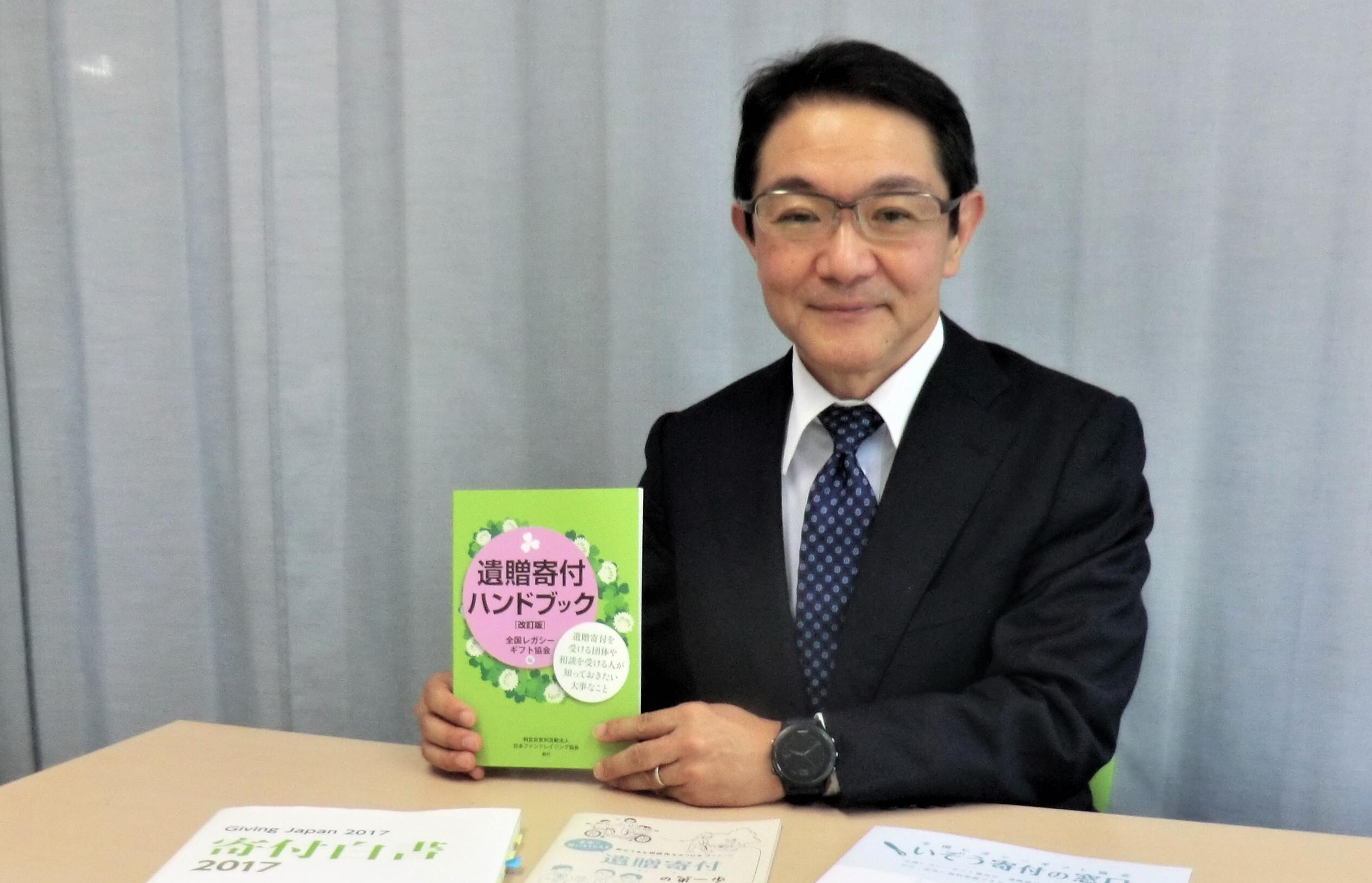 齋藤さんが遺贈寄付のハンドブックを手に微笑んでいる