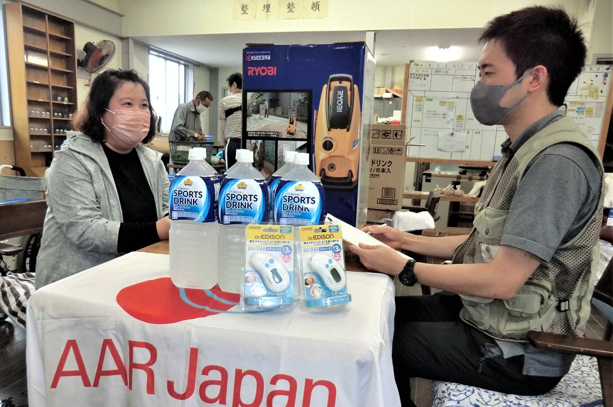 水などの物資を届け、事業所内の机に座りながら話を聞く生田目