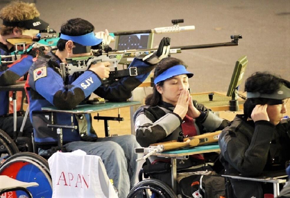 目をつむり集中力を高める田口さん。前後にもピストル銃を手にする競技者が並んでいる