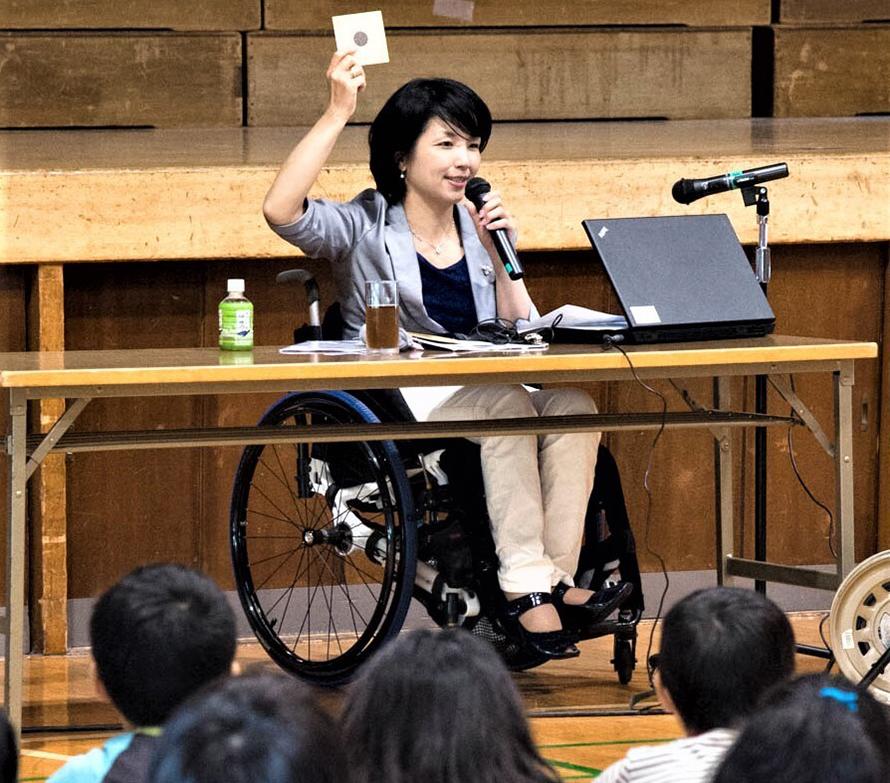 小さなカードなどを用いながら子どもたちに笑顔で話す田口さん 子どもたちの後ろ姿数名写っている