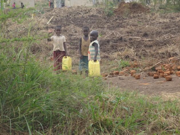 ポリタンクボトルに入った水を運ぶ子ども3人