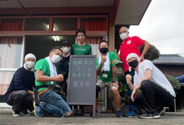 炊き出しを行うメンバー7人が建物の前でカメラに向かい力強く片方の腕をガッツポーズしてカメラに向かい微笑む