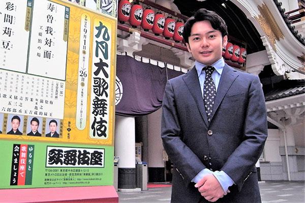 中村莟玉さんが歌舞伎座を背にして笑顔でこちらをみている グレイのスーツ姿