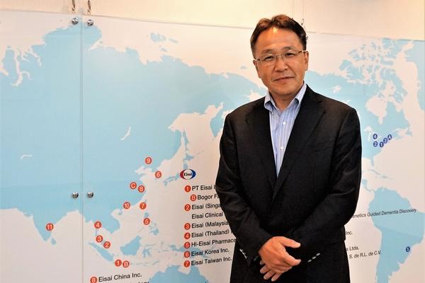 エーザイ株式会社の飛弾さんが、エーザイの活動地が載った世界地図の前で立っている