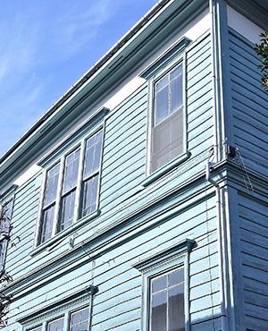 水色の外壁が青空のもとさわやかに生える