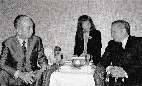 二人の男性が机を挟んで会談しており、その奥に女性が通訳をしている
