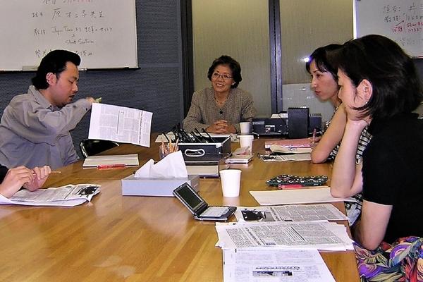 机を囲んで4人ほどが話している 机には電子辞書や書類が置かれている