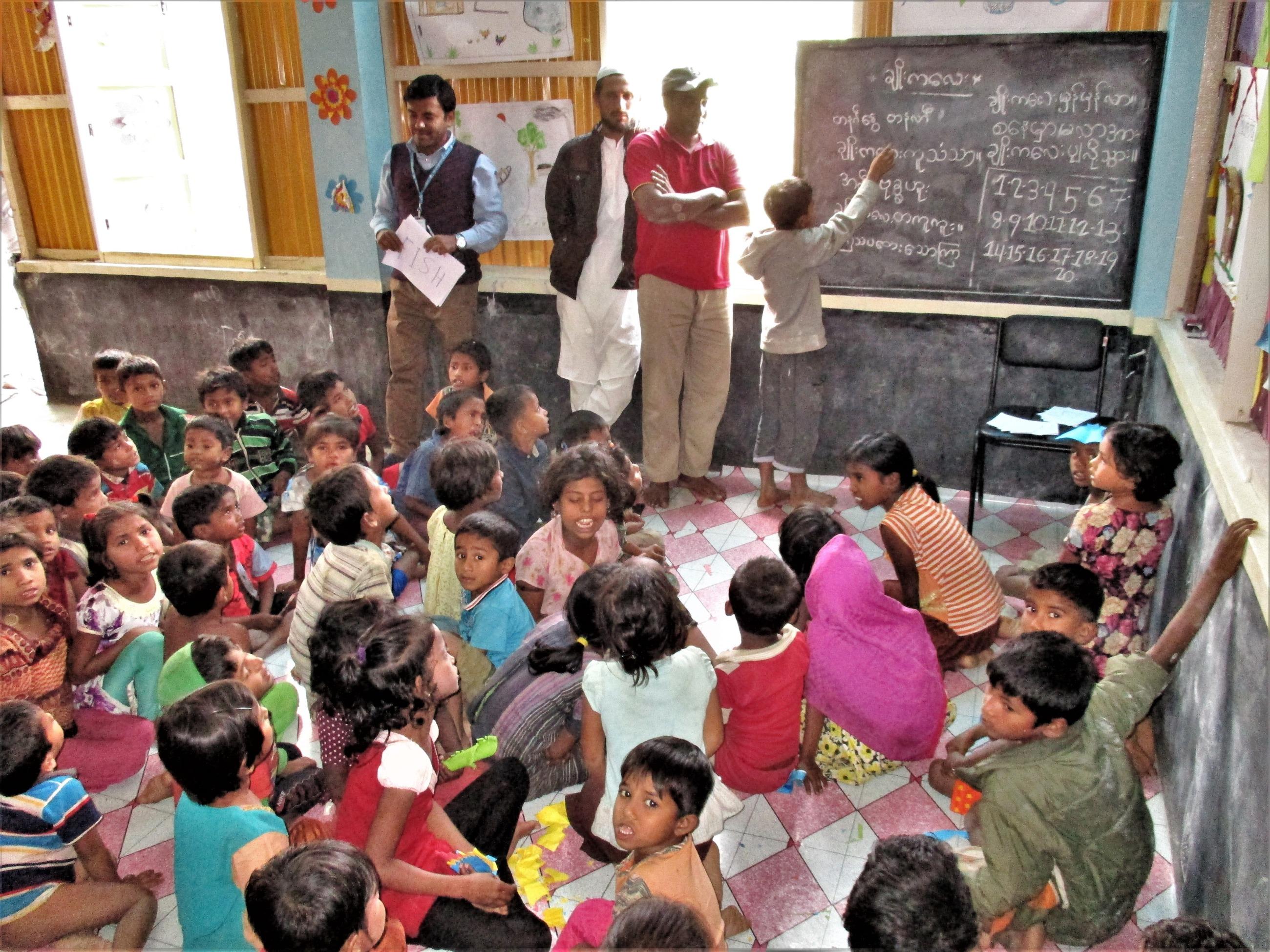 教室に多くの子供たちが集まり、男の子が黒板に何か書いている。