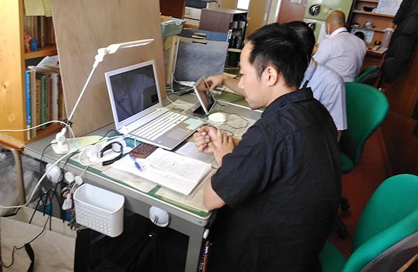 机上のパソコンに向かって話す大室 隣に先生が座り、PC操作など適宜サポートくださっている
