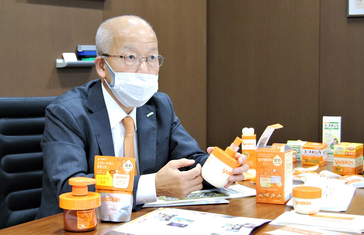 野渡社長が同社製品を手にしながら真剣な表情で話している